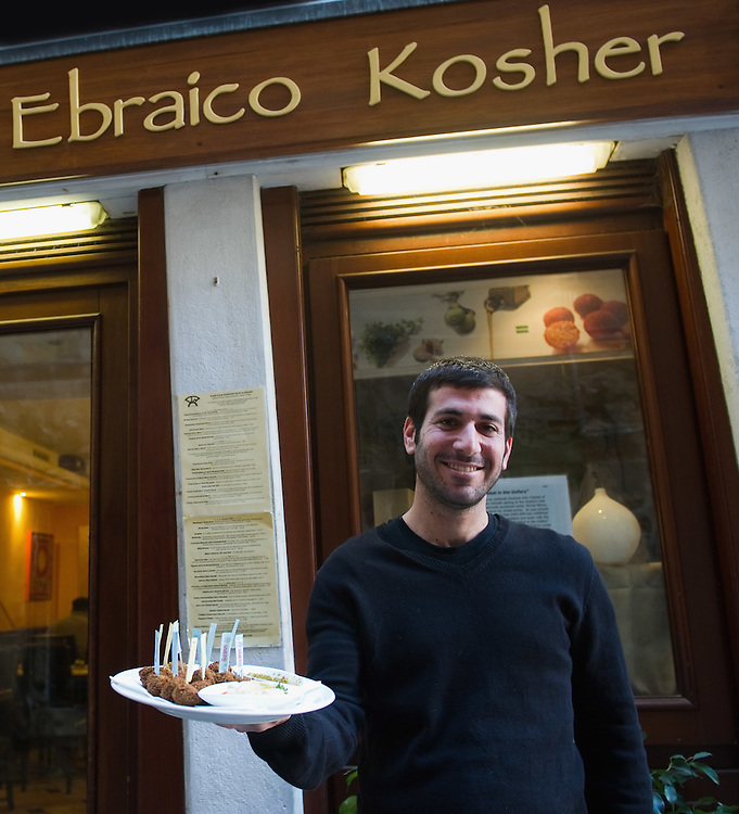 VENICE, ITALY - NOVEMBER 15: Member of staff Avishay offers appetizers in front of a koskher restaurant at the Venice Ghetto on November 15, 2011 in Venice, Italy. Established in 1516 the Ghetto of Venice was the area were Jews were compelled to live during the Venetian Republic. The English term 'ghetto' is derived from the Venetian term for 'slag' and refers to the refuse left the foundry that was located on the same island. In present times the ghetto is a multi-ethnical area area seen as the cultural heart of the city, but with five