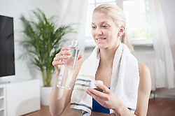 Young woman drinking water after exercise at living room and smiling, Bavaria, Germany