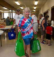 With their bags full Darlene and Peter carry them to their drivers for delivery for Week 1 of the Got Lunch Laconia program at the Congregational Church Monday morning.  (Karen Bobotas/for the Laconia Daily Sun)