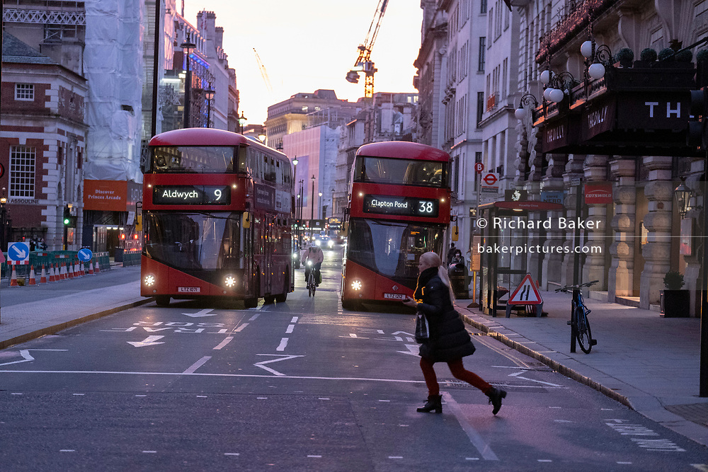 A young woman makes a last-minute evening dash across Piccadilly, in front of oncoming buses and other traffic, on 3rd February 2021, in London, England.