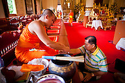 24 JUNE 2011 - CHIANG MAI, THAILAND: A monk blesses a man and ties a string to his wrist at Wat Phra Singh in Chiang Mai, Thailand. Wat Phra Singh is the most revered Buddhist temple in Chiang Mai because it houses the Phra Singh (Lion Buddha). The exact origin of the Buddha is unknown though it is known to have resided in Buddhist temples in Sukothai, Ayuthaya, Chiang Rai and Luang Prabang before coming to Chiang Mai in approximately 1360.  PHOTO BY JACK KURTZ