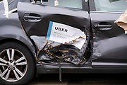 Smashed side of an Uber taxi where an accident has taken place while the ironic sign on the door says Uber: Be booked, be insured on 18th January 2020 in Birmingham, United Kingdom. Uber Technologies, Inc., commonly known as Uber, is an American technology company. Its services include ride-hailing, food delivery, package delivery, couriers, freight transportation, and, through a partnership with Lime, electric bicycle and motorized scooter rental.