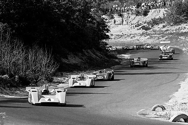 First Lap through Echo Valley at the old Bridgehampton circuit. Bruce McLaren leads Denny Hulme in their McLaren-Chevy M8s, with Peter Revson's Shelby American McLaren-Ford M6B on their heels. Eventual winner Mark Donohue is fourth in line here in his Penske McLaren M6B Chevy with Dan Gurney's McLeagle right behind. There are two winged cars, Jim Hall's Chaparral and John Surtees in a Lola.
