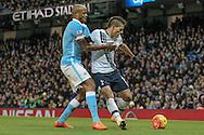 Érik Lamela (Tottenham Hotspur) runs the ball into the corner in injury time to count down the clock. Vincent Kompany (Captain) (Manchester City) comes across to tackle him during the Barclays Premier League match between Manchester City and Tottenham Hotspur at the Etihad Stadium, Manchester, England on 14 February 2016. Photo by Mark P Doherty.
