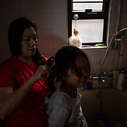Vanessa Mae Rodel, 42, fixes the hair of her seven-year-old daughter Keana Nihinsa, at their home in Hong Kong, on March 21, 2019. / Photo: Maria de la Guardia