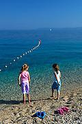 Two children (9 years old and 5 years old) wading at beach, Zlatni Rat, near Bol, island of Brac, Croatia