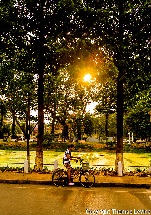 Bicycle Rider sitting in the sun in the late afternoon next to the river in Siem Reap. (Raw to Jpg), Vertical,