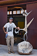 """Artist Kevin Box stands next to """"Conversation Peace"""" on the grounds at Box Studio on Saturday, July 18, 2020."""