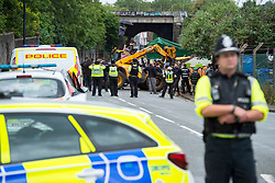 © Licensed to London News Pictures; 13/06/2020; Bristol, UK. New travellers facing eviction from the old gas works site on Glenfrome Road continue to block the entrance with a caravan and occupy a contractor's JCB into the evening after bailiffs from GRC arrived on Saturday morning with police also in attendance who have closed off the road. The travellers have been living on the site, which is owned by Wales and West Utilities, for some weeks, and say that the eviction is illegal and is being done without any court papers. The travellers have been told that this is a common law eviction, but they say it is illegal because there is building on the land (hidden by foliage) which is permanently occupied and so the land is ancillary to the building and so a possession order must be granted by a court before an eviction can take place, and that no possession order has been granted. Photo credit: Simon Chapman/LNP.