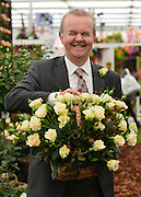 """© Licensed to London News Pictures. 20/05/2013. London, UK Ian Hislop holds up a basket of the """"Pride and Prejudice Rose"""". Press day at Chelsea Flower Show 2013. The centenary edition of the show attracts large number of visitors and is already sold out before opening day. Photo credit : Stephen Simpson/LNP"""