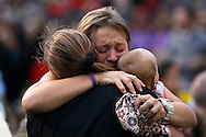 A woman holding a baby hugs another person seated in the section reserved for immediate family of the 19 firefighters killed in a nearby wildfire in Prescott, Arizona July 2, 2013. REUTERS/Rick Wilking (UNITED STATES)