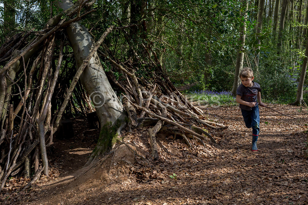 A seven year-old boy plays on his own by a wooden den, on 23rd April 2017, in Wrington, North Somerset, England.
