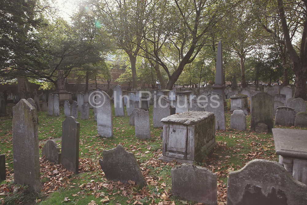 Bunhill Fields Burial Ground Cemetery on 10th October 2015 in London, United Kingdom. The former burial ground in the London Borough of Islington is now managed as a public garden by the City of London Corporation. It is about 1.6 hectares in extent and is the final resting place of William Blake, Daniel Defoe, John Bunyan and Susannah Wesley among others.