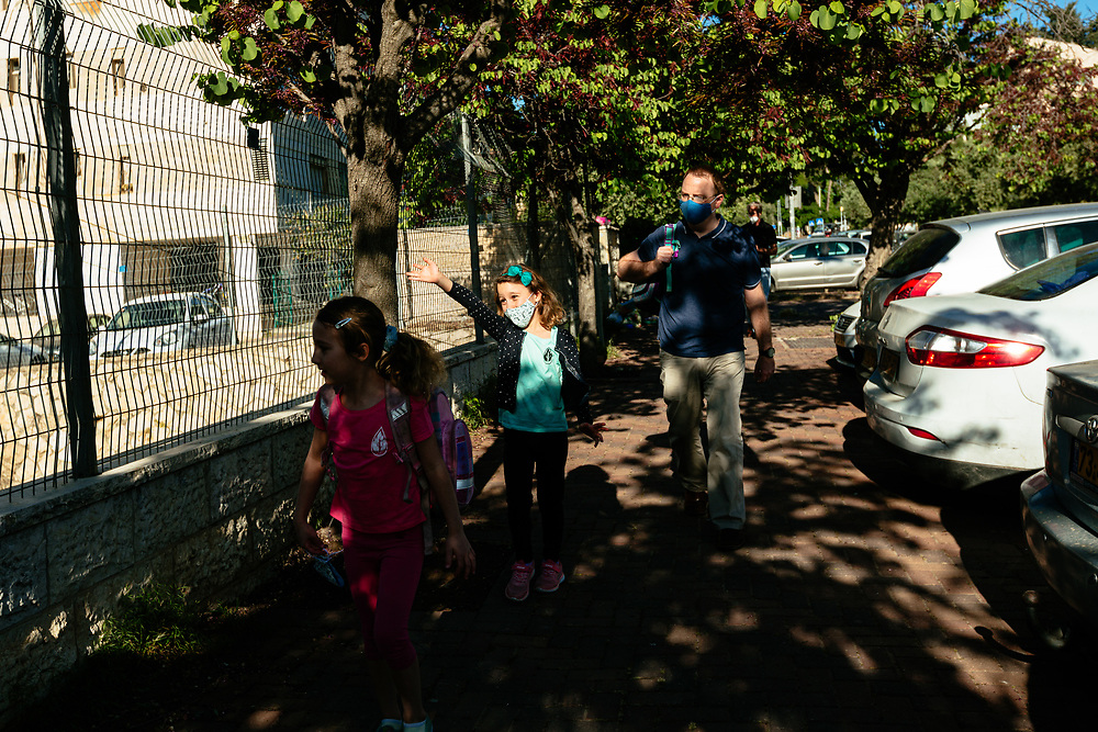 Twin girls Alma (C) and Clil (L), and their father Matti Michel, are seen as they walk towards the elementary school where the girls study, in Jerusalem, Israel, on May 3, 2020.