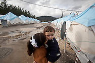 Bara'a kissed her younger cousin under rainy skies at Yayladagi refugee camp for Syrians in southern Turkey. 12/21/2012 Bradley Secker for the Washington Post