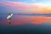 Surfer on the Beach at Low Tide at Sunset in Huntington Beach