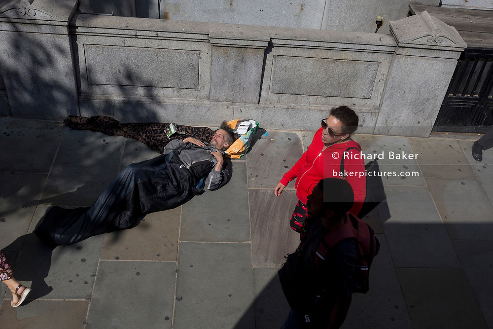 A lady in red walks past a homeless man lying asleep in a sleeping bag and lying across the pavement in Westminster, on 13th August 2019, in London England.