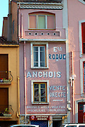 Etablissement Roque Anchois anchovies shop, house painted with advertising in white and pink. Collioure. Roussillon. France. Europe.