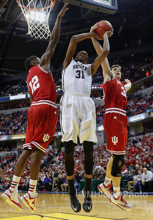 INDIANAPOLIS, IN - DECEMBER  20: Hanner Mosquera-Perea #12 and Collin Hartman #30 of the Indiana Hoosiers defend as Kameron Woods #31 of the Butler Bulldogs at Bankers Life Fieldhouse on December 20, 2014 in Indianapolis, Indiana. Indiana defeated Butler 82-73. (Photo by Michael Hickey/Getty Images) *** Local Caption *** Hanner Mosquera-Perea; Kameron Woods