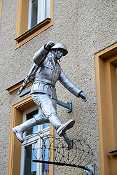 Statue of East German border guard escaping to freedom across Berlin Wall at Bernauer Strasse in Berlin Germany