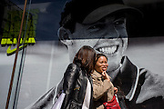 Smiling woman and friend pass a Nike retail poster of Northern Irish golfer Rory McIlroy, in central London.