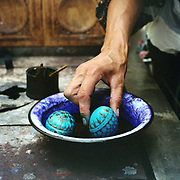 A woman dyeing painted eggs, Hurghis, Bucovina, Romania. In Christian Orthodox countries such as Romania there is a tradition of skilfully painting eggs before Easter. In the villages of Bucovina, the egg painters use a tool called a kishitze, a stick with an iron tip, to apply molten wax in the desired pattern to a blown egg. The egg is then dipped in the lightest colour dye to be used. The egg is then heated and the protective wax melts away and a new pattern can be added, then dipped in a different colour and so on.