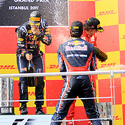 Red Bull Formula One driver Sebastian Vettel of Germany (L) celebrates with the trophy on the podium as team mate Mark Webber of Australia (F) and Ferrari Formula One driver Fernando Alonso of Spain (R) watch, after he won the Turkish F1 Grand Prix at the Istanbul Park circuit in Istanbul May 8, 2011. Photo by TURKPIX
