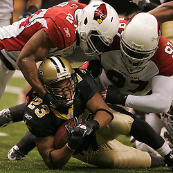16 January 2010:  Arizona Cardinals safety Adrian Wilson (24) and defensive end Bryan Robinson (97) combine to tackle New Orleans Saints running back Pierre Thomas (23) during a 45-14 win by the New Orleans Saints over the Arizona Cardinals in a 2010 NFC Divisional Playoff game at the Louisiana Superdome in New Orleans, Louisiana.