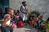 The Saxman of Abaco, Rashad Reckley plays his sax for hundreds of people gathered outside the Leonard M. Thompson International Airport in Abaco. on Thursday hoping to be evacuated off the island after Hurricane Dorian swept through the Bahamas. Relief flights are taking out the elderly and sick, but many say an air-bridge will be required to move all of those who want to leave the hard-hit northern islands of the Bahamas.
