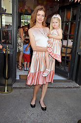 NATALIA VODIANOVA and her daughter NEVA PORTMAN at the 10th anniversary party of the store Caramel, Ledbury Road, London W11.  The party was held in association with the Naked Heart Foundation - a charity set up by model Natalia Vodianova.