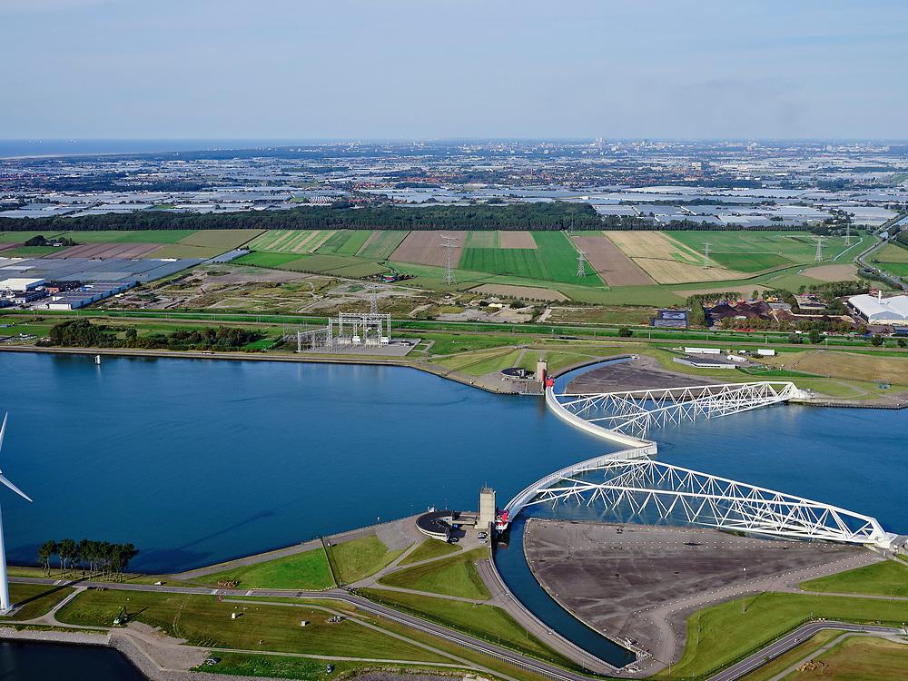 Nederland, Zuid-Holland, Hoek van Holland, 14-09-2019; Nieuwe Waterweg, Haven van Rotterdam. Functioneringssluiting Maeslantkering. De waterkering in de Nieuwe Waterweg wordt een maal per jaar, voordat het stormseizoen begint, getest. Tijdens het sluiten van de kering ligt alle scheepvaartverkeer naar de Rotterdamse haven stil. Kassen van het Westland in de achtergrond. De Maeslantkering sluit normaal gesproken alleen bij dreigende stromvloed en bij een waterstand van 3 meter of meer boven NAP. De kering, onderdeel van de Deltawerken, vormt samen met de Hartelkering de Europoortkering en beschermt Rotterdam en achterland bij extreme waterstanden.<br /> Hook of Holland - Port of Rotterdam. Aerial view of the new storm surge barrier (Maeslantkering) in the Nieuwe Waterweg during the so-called functioning closure, taking place one a year before the storm season begins. The waterway, leading to the Port of Rotterdam (at the horizon), is closed during the test. <br /> luchtfoto (toeslag op standard tarieven);<br /> aerial photo (additional fee required);<br /> copyright foto/photo Siebe Swart