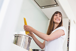 Mid adult woman cooking in kitchen, smiling