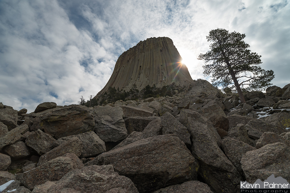 The sun peeks out from behind Devil's Tower as seen from the boulder field below.
