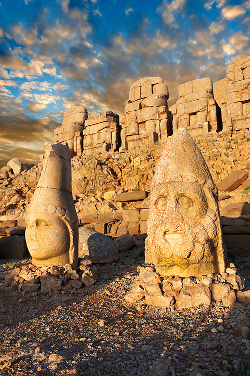 Image of the statues of around the tomb of Commagene King Antochus 1 on the top of Mount Nemrut, Turkey. Stock photos & Photo art prints. In 62 BC, King Antiochus I Theos of Commagene built on the mountain top a tomb-sanctuary flanked by huge statues (8–9 m/26–30 ft high) of himself, two lions, two eagles and various Greek, Armenian, and Iranian gods. The photos show the broken statues on the  2,134m (7,001ft)  mountain. 2