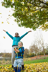 Mother and son enjoying by throwing autumn leaves in the air