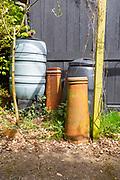 Garden corner details water butt chimney pots compost bin wooden post black shed,  UK
