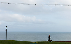 © Licensed to London News Pictures. <br /> 15/03/2015. <br /> <br /> Whitby, United Kingdom<br /> <br /> A man walks his dog along West Cliff in Whitby in North Yorkshire.<br /> <br /> Photo credit : Ian Forsyth/LNP