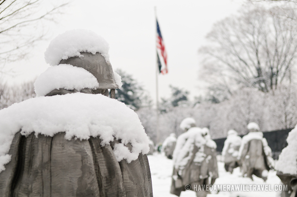 "The Korean War Memorial on the National Mall on a snowy winter morning, with the American flag in the distance. The Korean War Veterans Memorial, unveiled in 1992, sits on the northwestern end of the National Mall, not far from the Lincoln Memorial. It consists of several elements designed by different people and groups. It has a triangular footprint with the main elements being ""The Column"" consisting of 19 stainless steel solders, each over 7 feet tall, and a reflective granite wall etched with the faces of thousands of Americans who lost their lives in the war. At one end of the triangle, behind the soldiers, is a grove of trees. At the other is a large American flag and a small Pool of Remembrance. Among the designers were Frank Gaylord (the soldiers) and Louis Nelson (the reflecting granite wall)."