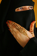 Dubai, United Arab Emirates. Portrait of a housewife at home. Her hands are adorned with henna in honor of the wedding she will attend this afternoon. She is covered from head to toe in her home today, as she is when out in public, because she is entertaining guests from outside her family.