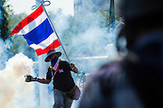 01 DECEMBER 2013 - BANGKOK, THAILAND: Thai anti-government protestors throw tear gas cannisters fired by riot police back towards the police lines during a riot in Bangkok. Thousands of anti-government Thais confronted riot police at Phanitchayakan Intersection, where Rama V and Phitsanoluk Roads intersect, next to Government House (the office of the Prime Minister). Protestors threw rocks, cherry bombs, small explosives and Molotov cocktails at police who responded with waves of tear gas and chemical dispersal weapons. At least four people were killed at a university in suburban Bangkok when gangs of pro-government and anti-government demonstrators clashed. This is the most serious political violence in Thailand since 2010.    PHOTO BY JACK KURTZ