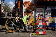 Workman feed yellow plastic tubing through an under pavement shaft to clear a subterranean blockage, working beneath a round pastry post ad. The works are outside a corner shop (store) in the south London district of Waterloo (celebrating the famous battle victory by Wellington over Napoleon in 1815) and the site is half-covered by a barrier that prevents pedestrians from falling down the opened manhole cover on the pavement (sidewalk). The two men force-feed the plastic piping to free whatever is obstructing the route to another site 50 metres down the street. The visual pun of the coiled cabling and the swirls of the Danish pastries make for a humorous scene.