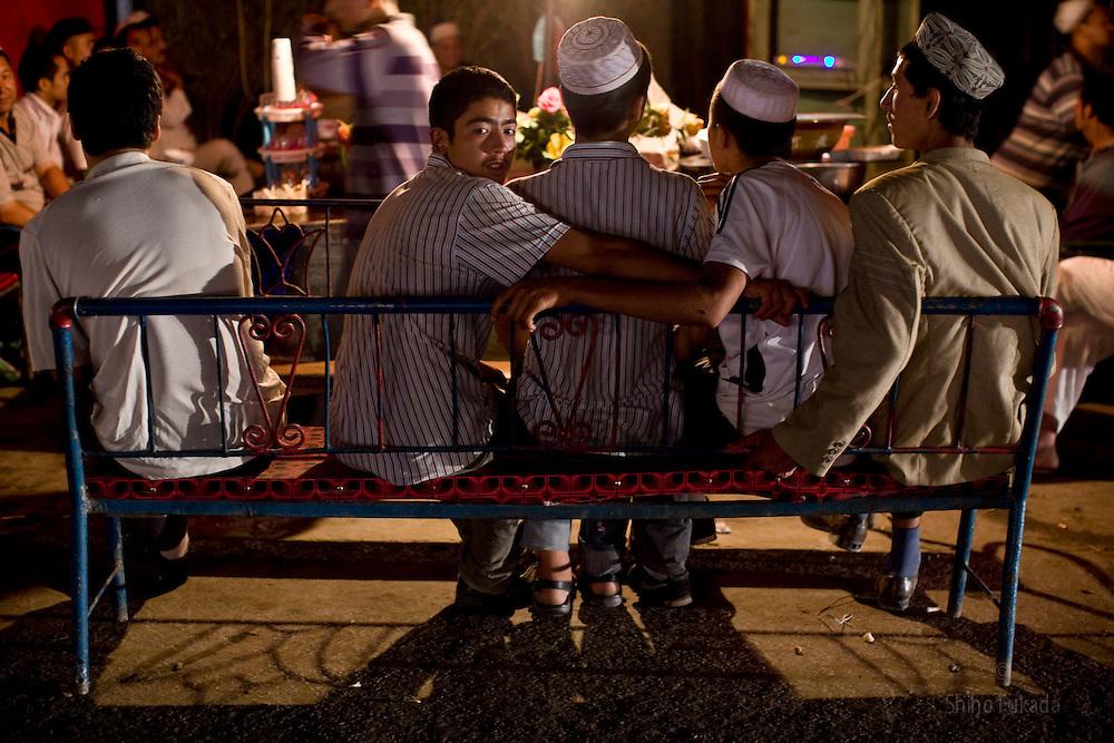 Uyghur men pass time at market in Hotan, Xinjian province in China.