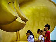 17 JULY 2017 - HUA TAPHON, ANG THONG, THAILAND: People pray at a fingernail of the big Buddha statue at Wat Muang in Ang Thong Province. The statue stands 92 m (300 ft) high, and is 63 m (210 ft) wide. Construction started in 1990, and completed in 2008. It is made of concrete and painted gold. The temple is renowned for the Buddha statue and its statue garden, which represents the Thai version of a hellish afterlife.      PHOTO BY JACK KURTZ
