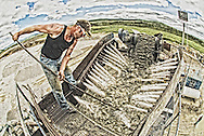 A gold mine worker feeds the gravel through the sluice in the Dawson gold fields.