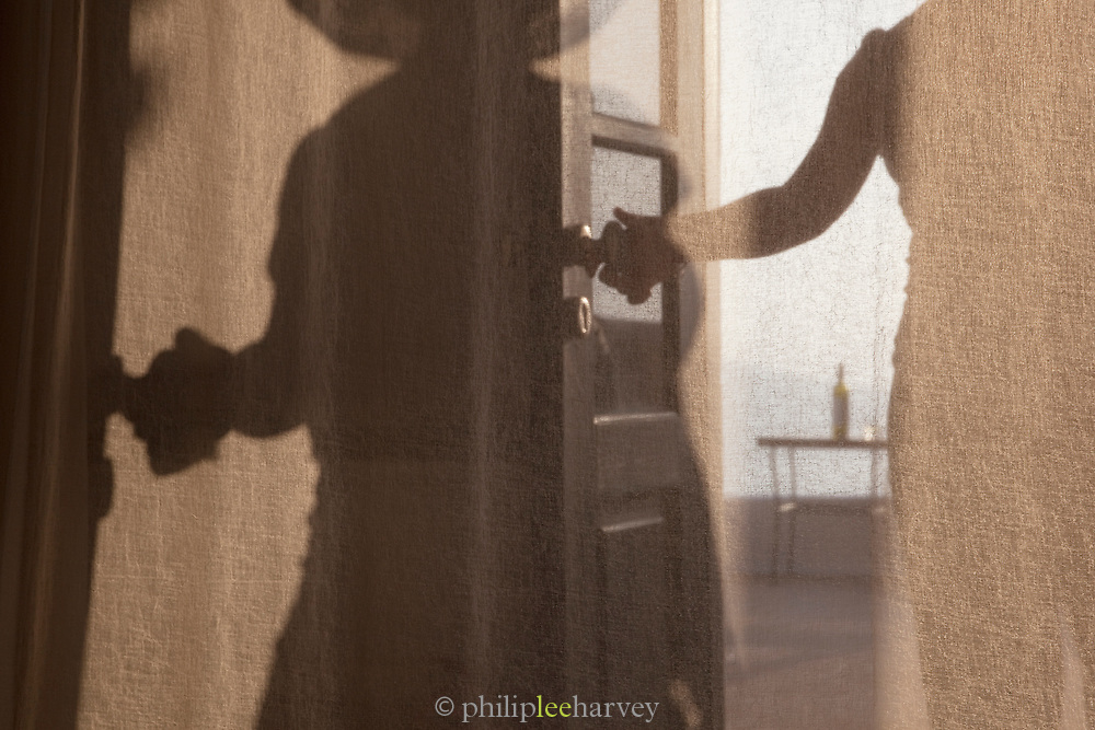 The shadow and silhouette of a woman closing the door to a balcony terrace of her hotel room in Santorini, Greece