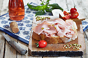 Mortadella with pistachio nuts on fresh bread slice, with cherry tomatoes, basil and rose sparkling wine.