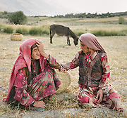 Mother and daughter gathering left over hay on their wheat field. The traditional life of the Wakhi people, in the Wakhan corridor, amongst the Pamir mountains.