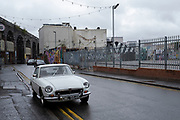 Old MGB GT classic car parked in Digbeth in Birmingham city centre, which is virtually deserted under Coronavirus lockdown on a wet rainy afternoon on 28th April 2020 in Birmingham, England, United Kingdom. Britains second city has been in a state of redevelopment for some years now, but with many outdated architectural remnants still remaining, on a grey day, the urban landscape appears as if frozen in time. Coronavirus or Covid-19 is a new respiratory illness that has not previously been seen in humans. While much or Europe has been placed into lockdown, the UK government has put in place more stringent rules as part of their long term strategy, and in particular social distancing.