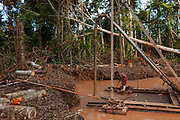 A miner adjusts the moorings of the machinery they use to extract gold in the Peruvian Amazon. Once they have finished extracting gold in that place, they will continue deforesting to extend the work area. Boca Colorado, Peru.