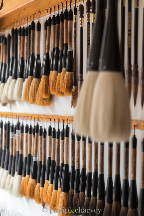 Lots of calligraphy brushes hanging on wall in shop for sale, Old Town, Tunxi district, Huangshan City, Anhui Province, China